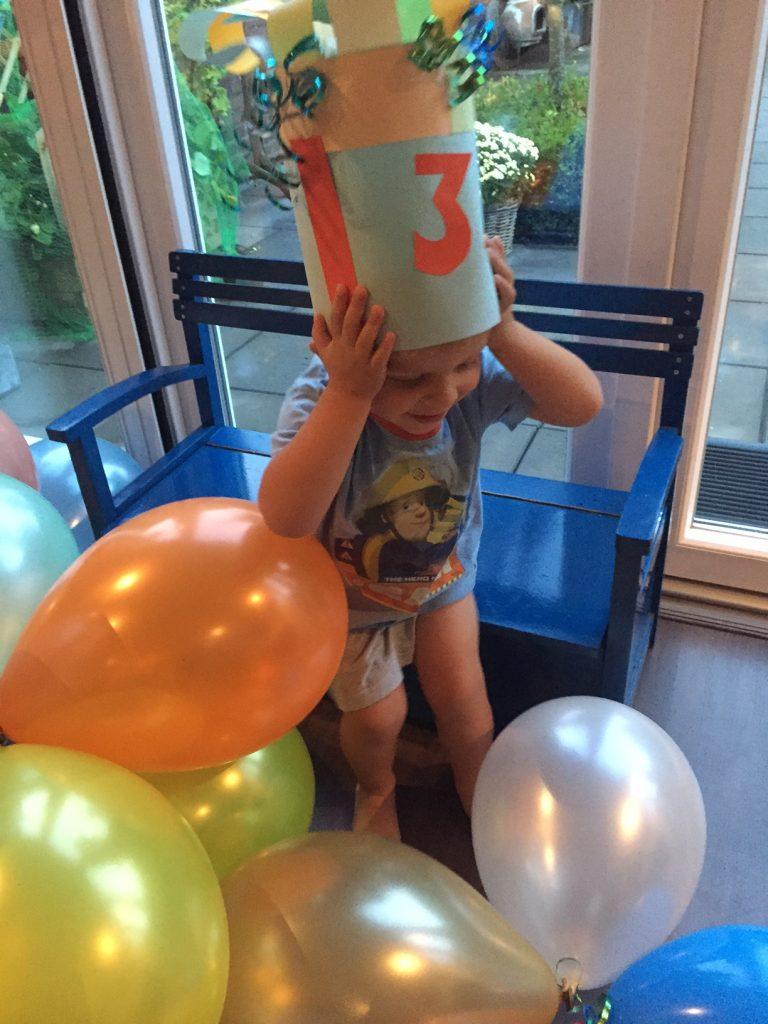 Verjaardagsmuts en tussen de ballonnen peuter verjaardag vieren blog Foodinista