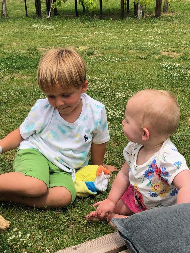 Broer en zus genieten spelend in het gras terwijl papa en mama een wijntje drinken in Toscane
